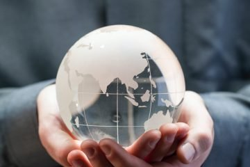 hands holding glass globe